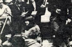 ULB, 1 juin 1968 : Ludo Martens debout en pull blanc sous le sigle SS à l'arrière-plan